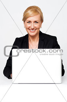 Aged corporate lady working on a laptop