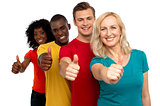 Smiling group of people with thumbs up gesture