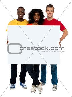 Smiling teenagers presenting blank billboard