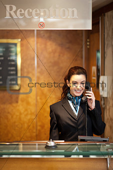 Attractive young receptionist receiving calls