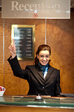 Beautiful female receptionist indicating upwards