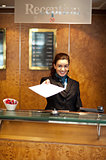 Female receptionist handing over check-out papers