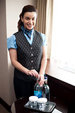 Cheerful waitress opening bottle of beverage