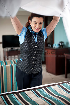 Charming female housekeeper replacing the sheets