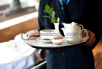 Cropped image of man carrying tea tray