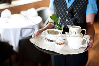 Cropped image of a woman holding tea tray