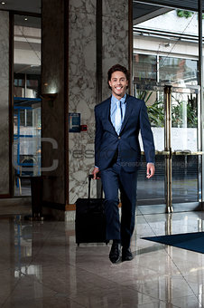 Business executive entering hotel lobby