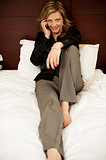 Pretty woman relaxing in bed and talking on phone