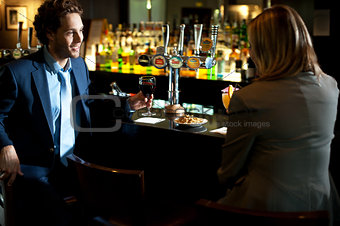 Attractive couple refreshing themselves at the bar