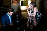 Woman enjoying cocktail and admiring man playing piano