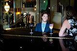 Couple enjoying soothing music as guy plans piano