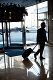 Man entering hotel lobby with his luggage