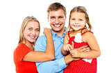 Cheerful family of three facing camera and smiling