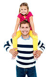 Fun loving kid sitting on her father's shoulders
