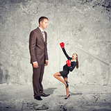 Large businessman looking at small businesswoman in boxing gloves. Concrete wall as backdrop