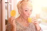 Woman Drinking Juice and Holding Orange Slice