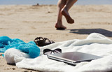 Wrap, laptop, scarf and mules on the beach