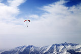 Paraglider silhouette of mountains in windy sky