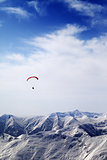 Parachutist silhouette of mountains in windy sky