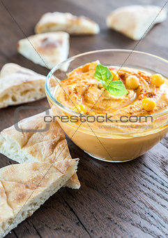 A bowl of hummus with pita slices