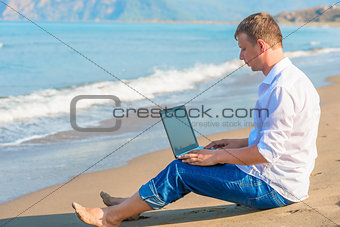 Free businessman working on a sandy beach