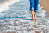 male legs in jeans walking along the sandy seashore