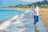 man in jeans and a white shirt walking along the seashore