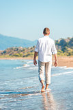 successful young man walking along a sandy beach