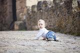 Little boy crawling on stone paved sidewalk