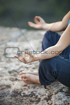 Close up of female hand zen gesturing. Girl sits in asana position.