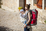 Young woman tourist carrying her little son in sling