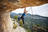 Young female rock climber struggling to make the next movement up