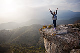 Young woman standing on cliff with outstretched arms and enjoying valley view