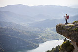 Young mother with baby in sling standing on cliff and enjoying valley view