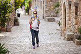 Young Caucasian woman tourist carrying her little son on shoulders while exploring old Spanish town