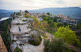Young couple standing on cliff and enjoying valley view of old village Siurana