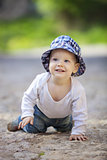 Cute little boy looking up and smiling while crawling on stone paved sidewalk