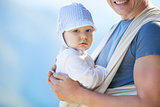 Cute toddler boy in sling, father carrying son outdoors