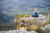 Young woman sitting on a rock in asana position