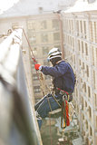 Industrial climber lowering from a roof of a building