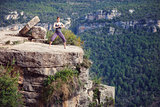 Young caucasian woman standing in yoga pose on top of cliff
