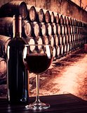 red wine glass near bottle in old wine cellar background