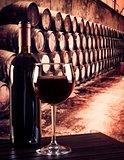 red wine glass near bottle in old wine cellar background
