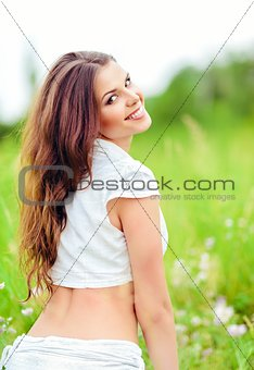 Portrait of cheerful smiling young woman in a field