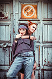 Two beautiful grunge girls standing at a wall