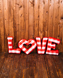 Love word of plush red letters on wood corner background. Full plaid textile