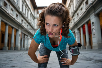 Fitness woman catching breathe near uffizi gallery in florence,