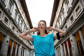 Fitness woman wearing earphones near uffizi gallery in florence,