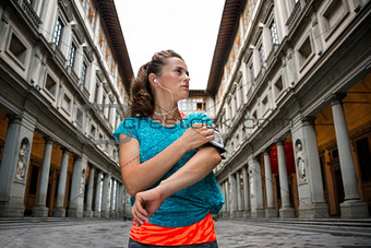 Fitness woman using cell phone near uffizi gallery in florence,