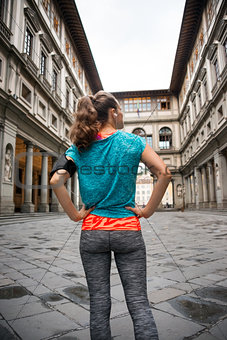 Fitness woman standing in front of uffizi gallery in florence, i